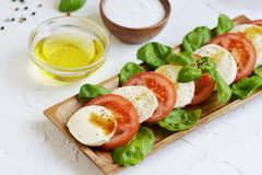 Mozzarella cheese with red tomatoes and basil leaves. Pepper, olive oil, wooden desk, healthy food concept, white background royalty free stock photography