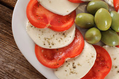 Mozzarella cheese slices with tomatoes and olives. Royalty Free Stock Photography