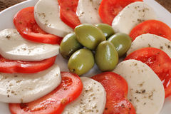Mozzarella cheese slices with tomatoes and olives. Royalty Free Stock Images