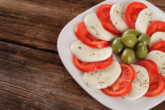 Mozzarella cheese slices with tomatoes and olives. Stock Photography