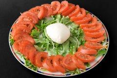 Mozzarella cheese and tomato. Mozzarella chesse tomato and rocket on a plate. Black background Royalty Free Stock Image