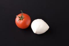 Mozzarella cheese and tomato. Mozzarella chesse tomato on a black background Royalty Free Stock Photos