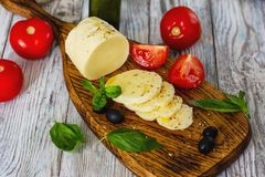 Mozzarella cheese with tomatoes and Basil on wooden background royalty free stock photo