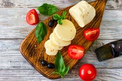 Mozzarella cheese with tomatoes and Basil on wooden background, stock photos