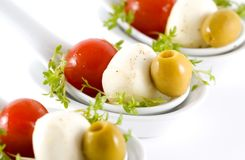 Mozzarella, cherry tomatoes and olives garnished w. Ith cress salad, served in an individual white ceramic spoons Royalty Free Stock Photography