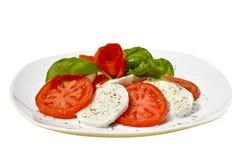 Mozzarella con i pomodori su fondo bianco Fotografia Stock