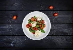Mozzarella con los tomates de cereza, la salsa del pesto y la albahaca asados a la parrilla fotografía de archivo libre de regalías