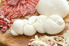 Mozzarella on cutting board with salami and cheese. Royalty Free Stock Images