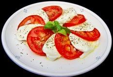 Mozzarella di bufala and tomato salad. On black royalty free stock photos