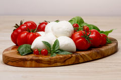 Mozzarella, heirloom tomatoes, basil leaves on a wooden serving Stock Photography