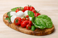 Mozzarella, heirloom tomatoes, basil leaves on a wooden serving Royalty Free Stock Photos