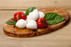 Mozzarella, heirloom tomatoes, basil leaves on a wooden serving Royalty Free Stock Image