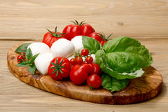 Mozzarella, heirloom tomatoes, basil leaves on a wooden serving Royalty Free Stock Photo