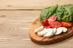 Mozzarella, heirloom tomatoes, basil leaves on a wooden serving Royalty Free Stock Images