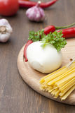 Mozzarella with herbs, noodles, fresh vegetables, chilli, garlic on a wooden round board Royalty Free Stock Image