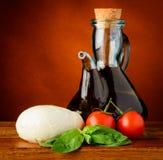 Mozzarella, Olivenöl, Basilikum und Tomaten Stockbild