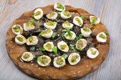 Mozzarella pieces with pesto, basil and olive oil Stock Photos