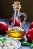 Mozzarella, pomodori rossi e basilico fresco su un fondo nero Fotografie Stock Libere da Diritti