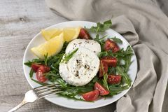 Mozzarella salad with arugula. Cherry tomatoes, lemon, seasoned with spices and olive oil stock image