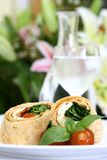 Mozzarella and spinach tortilla. A plate of mozzarella and spinach tortilla wrap sandwich with cherry tomatoes Royalty Free Stock Image