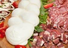 Mozzarella sul tagliere con salame e formaggio Immagine Stock