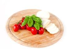 Mozzarella, Tomaten und Basilikum auf hölzernem Vorstand lizenzfreie stockbilder