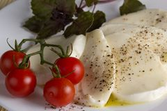 Mozzarella tomato basil and oil. Dish on a white plate of mozzarella tomato basil and oil, pepper Royalty Free Stock Photography
