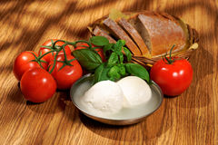 Mozzarella, tomatoes, basil, bread, composition on a wooden table Stock Image