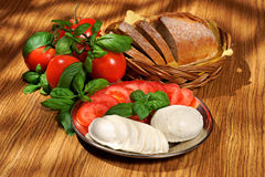 Mozzarella, tomatoes, basil, bread, composition on a wooden table Stock Photography
