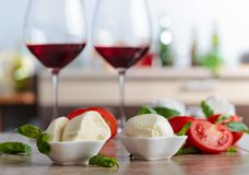 Mozzarella with tomatoes , basil and glasses of red wine . Royalty Free Stock Photos