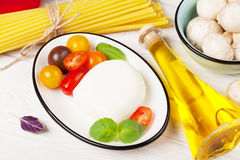 Mozzarella, tomatoes, basil and olive oil Stock Photos