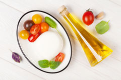 Mozzarella, tomatoes, basil and olive oil Stock Images