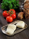 Mozzarella, tomatoes, bread, basil, composition on a wooden table Royalty Free Stock Photo