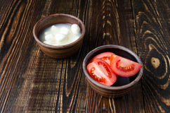 Mozzarella and tomatoes in a clay plate. On a wooden table made of dark hardwood royalty free stock images