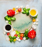 Mozzarella tomatoes salad ingredients with basil,oil and balsamic vinegar around empty plate on rustic wooden background, top view. Copy space royalty free stock photography