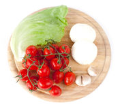 Mozzarella and vegetables on wooden board. Mozzarella and vegetables on white royalty free stock photo