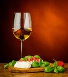 Mozzarellakäse, -basilikum, -tomaten und -wein Lizenzfreie Stockbilder