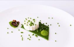 Mozzarellapudding, spenatkaviar, spenatsås och gräsplanpape Arkivbild
