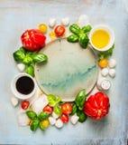 Mozzarellatomaten-Salatbestandteile mit Basilikum, Öl und Balsamico-Essig um leere Platte auf rustikalem hölzernem Hintergrund, D Lizenzfreie Stockfotografie