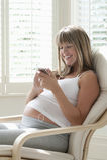 从MP3播放器的孕妇听的音乐 库存照片
