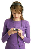 Mp3. Girl searching for good music on her mp3 player Stock Photography