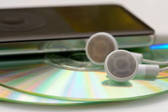 MP3 Music. MP3 player and ear phones on top of CDs Royalty Free Stock Photography