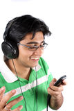 Mp3 Phone. An Indian teenager listening to music on his headphones and a MP3 cellphone, on white studio background Stock Photos