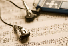 MP3 player and earphones on a music sheet royalty free stock photos