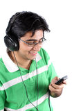 MP3 Teenager. An Indian teenage boy in a green t-shirt, listening to music on his MP3 player, on a white background Stock Image