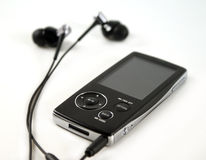 MP4 PLAYER. A black mp4 player with a par of modern headphones Royalty Free Stock Photography