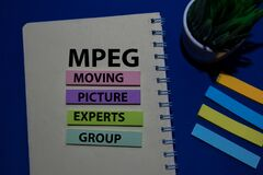 MPEG - Moving Picture Experts Group acronym write on sticky note isolated on Office Desk