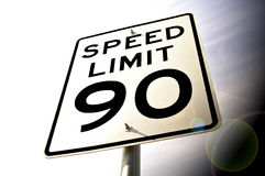 90 MPH. A bright 90 MPH Speed Limit Sign with Sun Flare Royalty Free Stock Photography