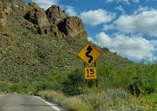 15 mph de la advertencia para las curvas en camino a continuación imagenes de archivo