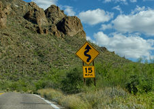 15 mph warning for curves in road ahead Royalty Free Stock Photography